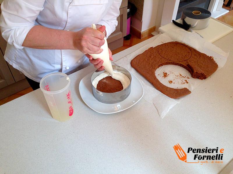 Primo strato di pan di spagna della fetta al latte mentre viene farcito