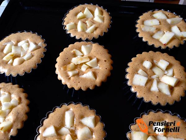 Le mele sono aggiunte al composto e le tortine sono pronte per la cottura